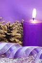 Christmas candle scene with burning and gift ribbon in lilac tone Royalty Free Stock Photo