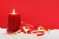 Christmas candle on snow red background a sitting in with ribbons against a add your own festive message Royalty Free Stock Photo