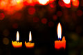 Christmas candle three red with a bokeh lights Royalty Free Stock Photo