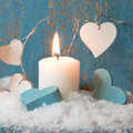 Christmas candle in white with blue hearts, wood and snow for de Royalty Free Stock Photo