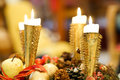 Christmas candles four burning brightly in gold candlestick holders with an apple fir cone and other decorations below Stock Photography