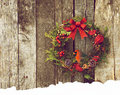 Christmas card background wreath with natural decorations with a beautiful male northern cardinal peeking out hanging on a rustic Royalty Free Stock Photography