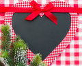 Christmas card blank in heart shape with bow and branch on red gingham tablecloth Royalty Free Stock Photo