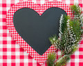 Christmas card blank in heart shape with branch of tree on red gingham tablecloth winter holidays concept Stock Image