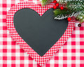Christmas card blank in heart shape with branch of tree on red gingham tablecloth winter holidays concept Royalty Free Stock Image