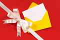 Christmas card diagonal gift ribbon bow red paper background copy space with and in white satin on with yellow envelope and blank Stock Photos