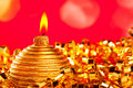 Christmas card of golden bauble candle on tinsel Royalty Free Stock Photo