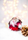 Christmas card with handmade bauble and cone with festive decora decorations lights twinkling ball on white snow Stock Image