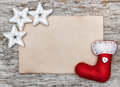 Christmas card with sheet of paper and red sock on the old wood background Stock Photo