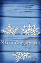 Christmas card with snowflakes on blue wooden background and greetings vintage Stock Image