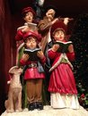 Christmas carolers withe red coats and Royalty Free Stock Photo
