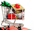 Christmas cart a shopping with items sitting on top of a present Royalty Free Stock Photo