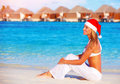Christmas celebration on maldive island beautiful young woman celebrating holiday wearing red santa hat sitting the beach luxury Royalty Free Stock Photos