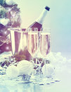 Christmas celebration. Two flutes and bottle of champagne over decorated Christmas tree Royalty Free Stock Photo