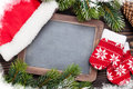 Christmas chalkboard, mittens, santa hat and tree Royalty Free Stock Photo