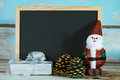 Christmas chalkboard with santa claus and white gift box over gr grunge blue wood background Stock Image