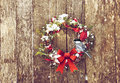 Christmas chickadee wreath with natural decorations with a cute perched hanging on a rustic wooden wall with copy space Royalty Free Stock Photos