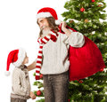 Christmas child santa claus grandfather with red and bag in front fir tree Stock Photo
