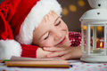 Christmas child writing letter to Santa in red hat Royalty Free Stock Photo