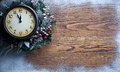 Christmas clock over snow wooden background five to twelve Royalty Free Stock Images