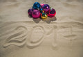 Christmas colored balls lie on the beach, next to the sand, the date is written. Royalty Free Stock Photo