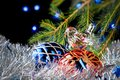 Christmas decorations lying in tinsel and fir branches on a dark background with blurred lights Royalty Free Stock Photo