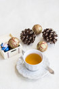 Christmas composition with cup of tea balls and bumps on a white cloth Royalty Free Stock Images