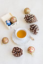 Christmas composition with cup of tea balls and bumps on a white cloth Stock Photography