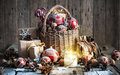 Christmas composition with gifts and burning candle vintage sty basket red balls pine cones snowflakes on wooden table style Royalty Free Stock Image