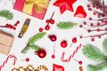 Christmas composition with golden garland, red gift, green Xmas fir branch, red holly berries and baubles on white stucco plaster Royalty Free Stock Photo