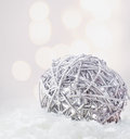 Christmas composition with silver bauble and snow on defocused bokeh background snowflakes Royalty Free Stock Photo