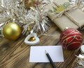 Christmas composition with tinsel, baubles, lights, gift and card  on the wooden background Royalty Free Stock Photo