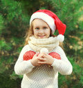 Christmas concept - little smiling girl child in santa red hat with balls Royalty Free Stock Photo