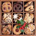 Christmas cookies assorted in wooden box with holly sprig Royalty Free Stock Images
