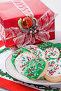 Christmas cookies and a red package on a holiday themed place mat Royalty Free Stock Photo