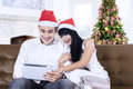 Christmas couple with digital tablet portrait of happy at home Royalty Free Stock Photo
