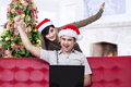 Christmas couple expressing success at home asian boyfriend is shouting happily looking laptop Stock Image