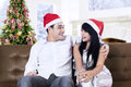 Christmas couple wearing santa hats smiling at home Stock Photos