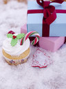 Christmas cupcake beside a gift box Stock Photos