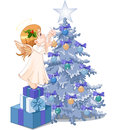 Christmas cute angel decorating tree Stock Photography