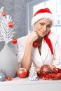 Christmas daydreaming smiling woman in santa claus hat while decorating for Royalty Free Stock Image