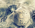 Christmas decoration. Christmas ball, pine cones, glittery jewels on white satin. Royalty Free Stock Photo