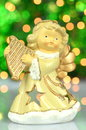 Christmas decoration figure of angel playing the harp against bokeh background Stock Photos