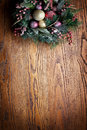 Christmas decoration with fir and baubles over wooden background Royalty Free Stock Image