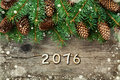 Christmas decoration of fir tree and conifer cone on textured wood background, magic snow effect and wooden numbers of New year Royalty Free Stock Photo