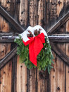 Christmas decoration on old barn of red ribbon and evergreen boughs hanging weathered door and covered with snow in jacksonville Royalty Free Stock Photography