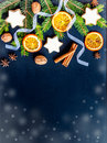 Christmas decoration over dark wood background. Top view of homemade butter nuts star shaped cookies with icing, pine, orange slic Royalty Free Stock Photo