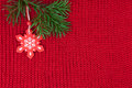 Christmas decoration over red wool knitted fabric winter background of with Stock Images