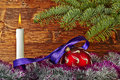 Christmas decoration red ball violet ribbon fir tree candle and wooden background selective focus Stock Images