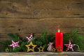 Christmas decoration: red candle and brunches on wooden old back Royalty Free Stock Photo